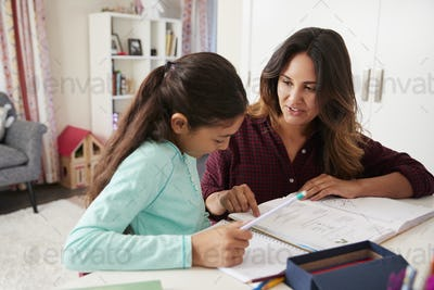 Mother Helping Daughter With Homework Sitting At Desk In Bedroom