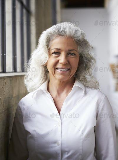 Senior white businesswoman in white shirt, vertical