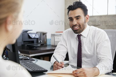 Young Hispanic male professional in meeting with woman in office