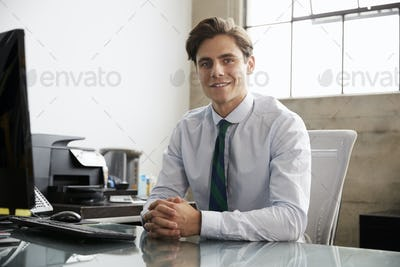 Young white businessman at an office desk, smiling to camera