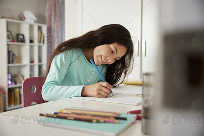 Young Girl Sitting At Desk In Bedroom Doing Homework