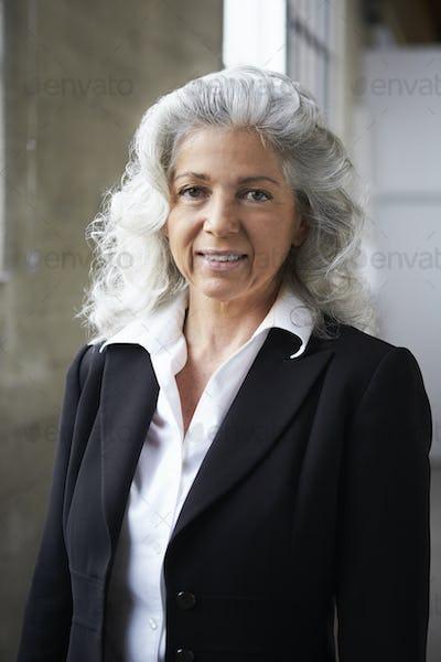 Senior white businesswoman smiling to camera, vertical