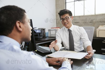 Young Asian professional in meeting with mixed race man