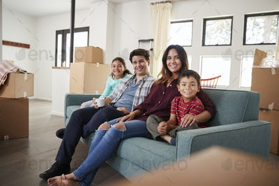 Portrait Of Happy Family Resting On Sofa Surrounded By Boxes In New Home On Moving Day