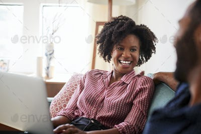 Couple Sitting On Sofa At Home With Woman Using Laptop Computer