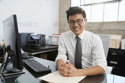 Young Asian male professional at desk smiling to camera