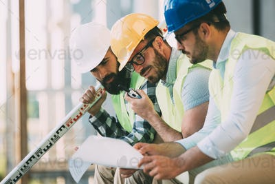 Portrait of construction engineers working on building site