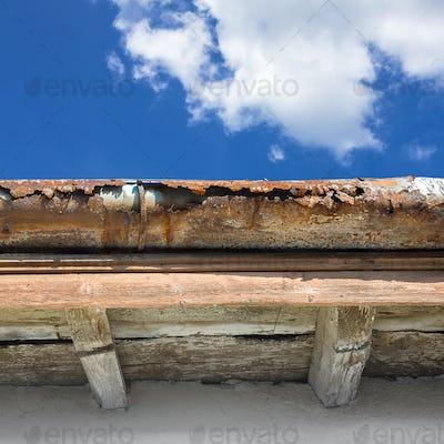 Old gutter against blue sky