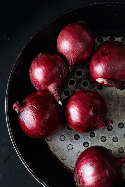 Sliced red spanish onion on vintage frying pan