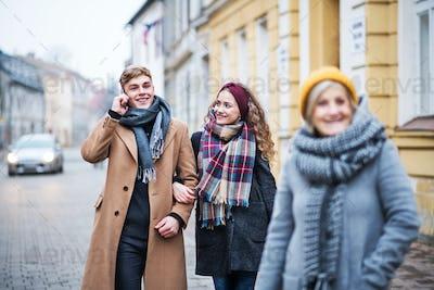 Grandmother and teenage grandchildren walking down the street in winter.