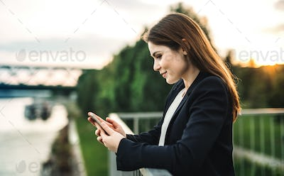 A young businesswoman standing on the river bank, using smartphone.