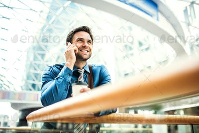 A young businessman with smartphone standing in a modern building, making a phone call.