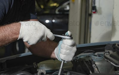 Close up hands in white textile gloves of mechanic doing car service
