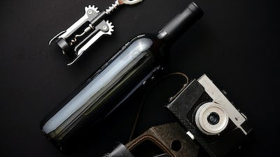 Red wine bottle, corkscrew and old photo camera