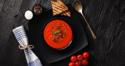 Tomato soup in black bowl with crisp bread