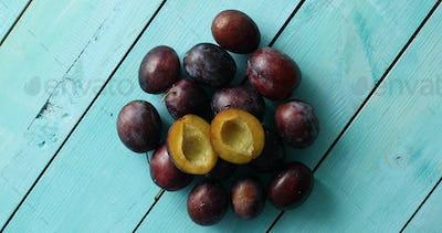 Pile of ripe plums on blue wood