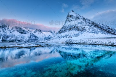 Beautiful snow covered mountains and blue sky reflected in water