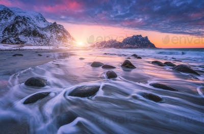 Amazing sandy beach with stones in blurred water at sunset