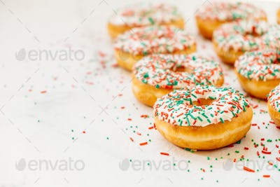 Donuts with white chocolate cream and sprinkles sugar