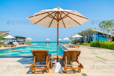 Beautiful umbrella and chair around swimming pool in hotel and r