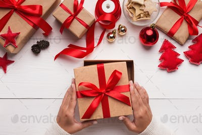 Female hands of opening her Christmas gift