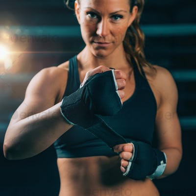 Female boxer wrapping hands