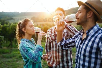 Wine growers tasting wine in vineyard