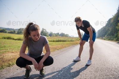 young couple warming up and stretching on a country road