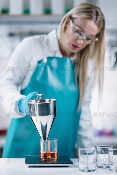 Female Candle Maker Pouring And Measuring Melted Orange Wax