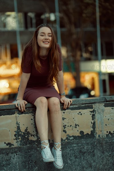 Beautiful lonely girl sitting in the city with light in the back