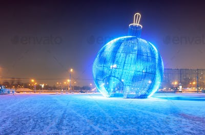 Giant luminous glowing blue Christmas ball on the street at night