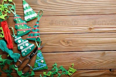 Handmade rustic green felt Christmas tree decorations and scisso
