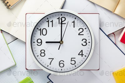 wall clock and open notebook or book
