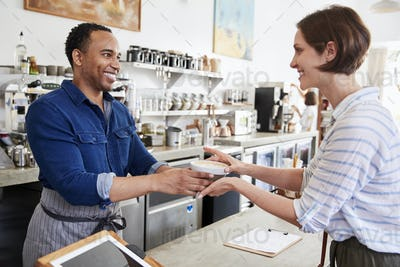 Male barista passing coffee to a female coffee shop customer