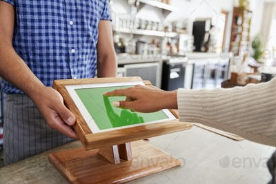 Customer using touch screen sales terminal at cafe, close up