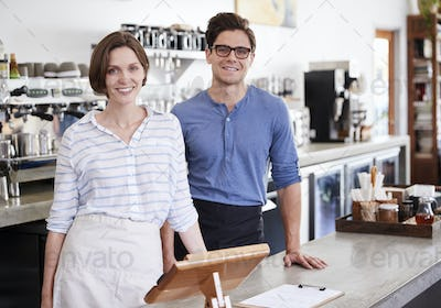Happy young man and woman behind the counter at coffee shop