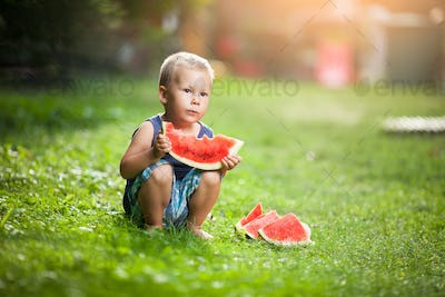 Cute toddler eating a slice of watermelon