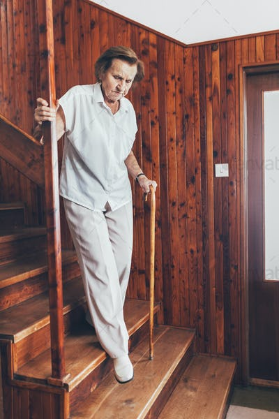 Elderly woman at home using a cane to get down the stairs