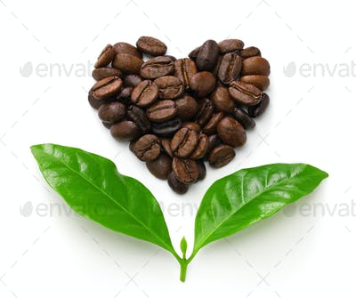 heart shaped roasted coffee beans and leaves, fair trade concept image isolated on white background
