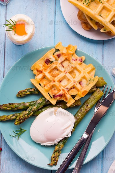 Grilled waffle with Green boiled Asparagus with Poached Egg, with salt and spices on blue plate as a