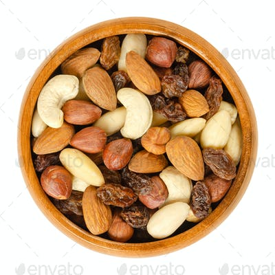 Nuts and raisins in wooden bowl over white