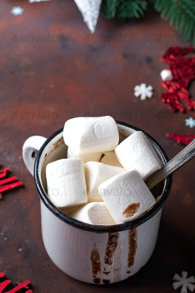 Winter hot drink close up. Hot chocolate or cocoa with marshmallow and spices on dark stone