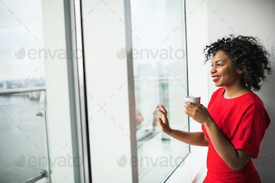 A woman standing by the window holding coffee cup, looking out. Copy space.