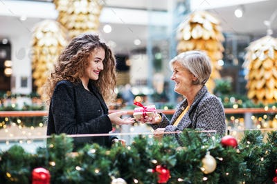 A teenage girl giving present to grandmother in shopping center at Christmas.