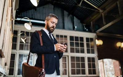 A waist up portrait of businessman with smartphone standing in city.