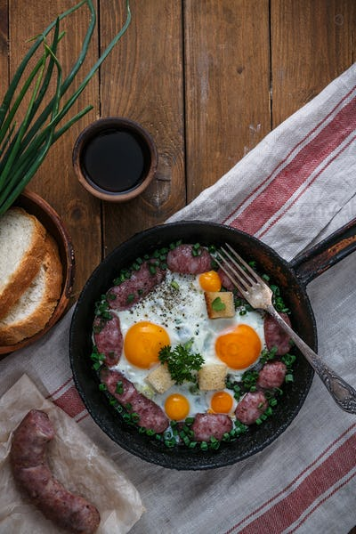 Frying pan with tasty cooked egg and sausages on table, copy space
