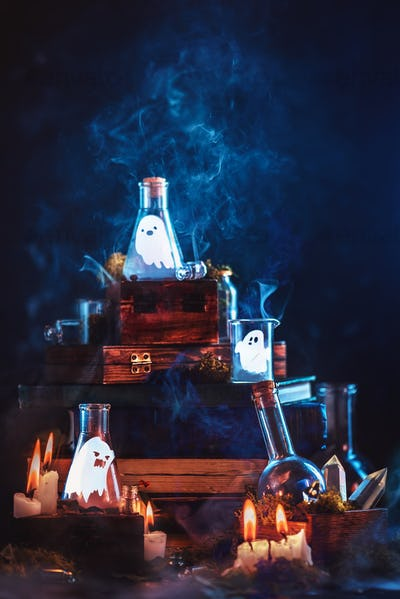 Little ghosts in glass jars. Halloween concept on a dark background with a stack of magical books