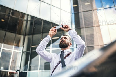 Hipster businessman with smartphone standing on the street in London, taking selfie.