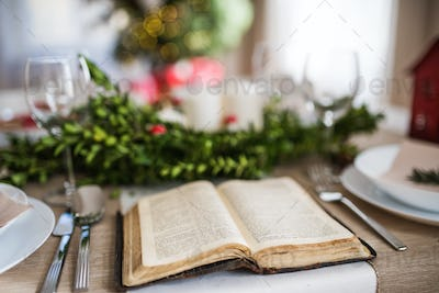 Holy bible book on a table set for a dinner at home at Christmas time.
