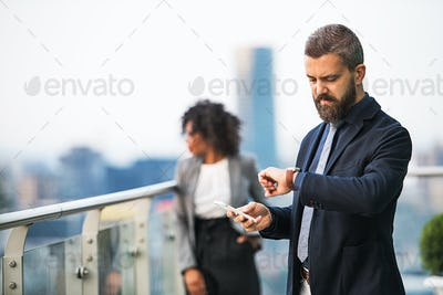 A portrait of a businessman with smartphone standing on a terrace.